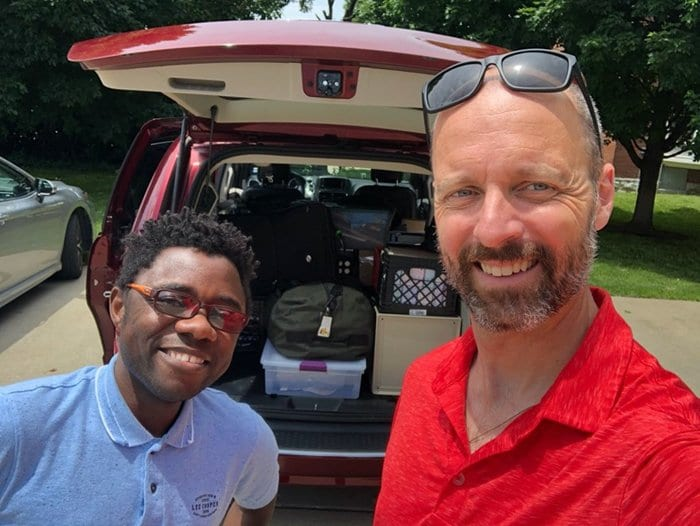 Fr. Laramie (right) with Fr. Armel Setubi, SJ, loading the red minivan.